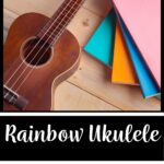 """A picture of a wooden ukulele laying flat next to a pile of multicolored books. The words on the image read """"Rainbow Ukulele: Student Method Book"""""""